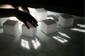 Counselling and life coaching: the hands of a counsellor in shadow, move the pieces around, white cubes in the reflected light of windows above