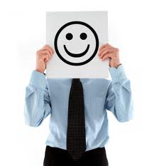 A business man in a suit holds up a sign of a smiley face to cover his real face.