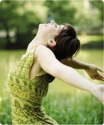 Experiencing happiness, young woman in green dress throws back her arms and head, eyes closed, lush green vegetation and river in the background