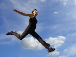 Woman leaps with renewed self esteem into a new day, the image of sky and clouds surrounding her