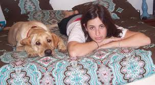 A young girl and her labrador are lying on her bed, looking out at us with similar expressions of sadness, yet they are together.