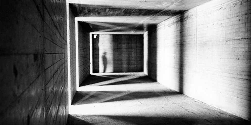 A black and white corridor with light beaming in through the cracks. Counselling can shine lights on things you cannot currently see. There is a silhouette shadow of a man at the end of the corridor