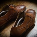 This image is of an empty pair of leather shoes on a wooden floor, lit by a spotlight. The caption is a question: Compare yourself with others?