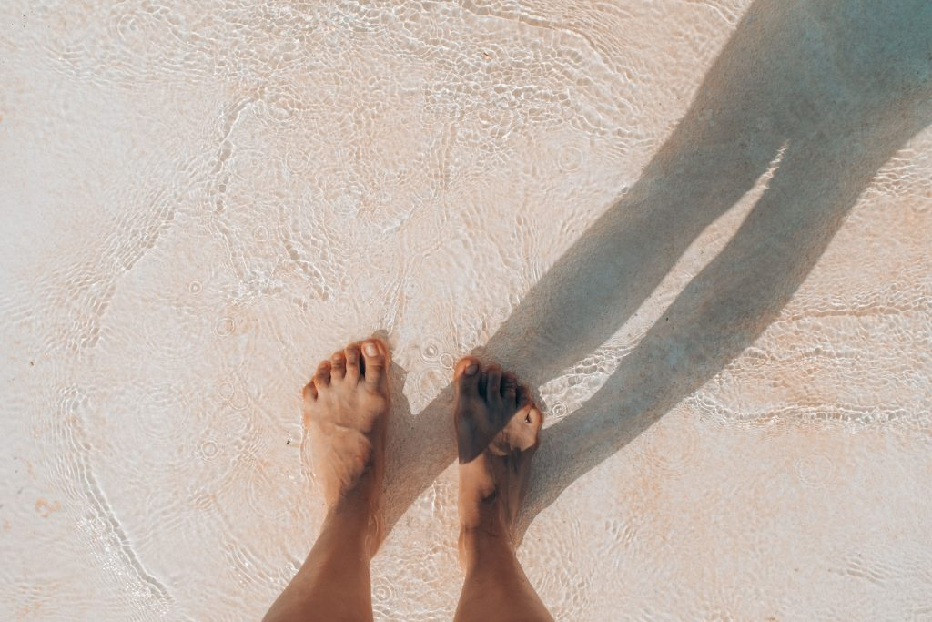 Man's feet standing in the shallows of the ocean