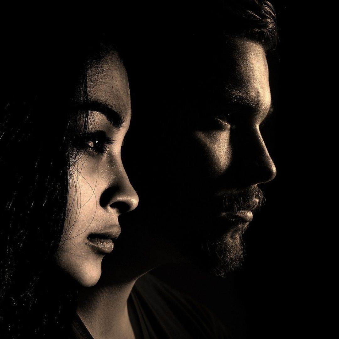 Side on view of a man and woman looking forward emotionless and a dim light illuminating the left side of their face