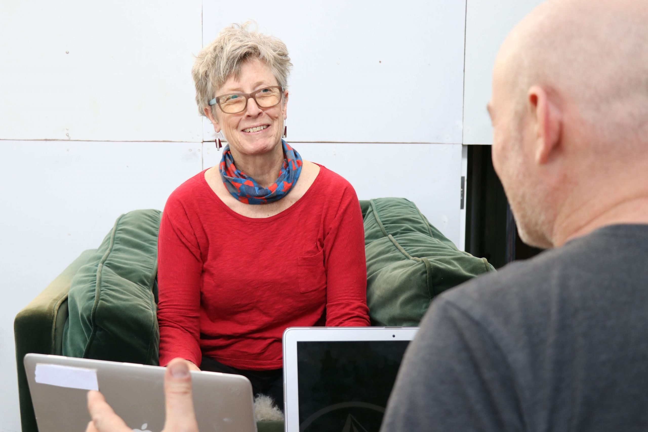 Linda Magson, Clinical Supervisor for Counsellors and Psychotherapists wearing a red sweater and smiling, sitting on a green couch in front of a bald man who is showing her something on a grey notebook computer