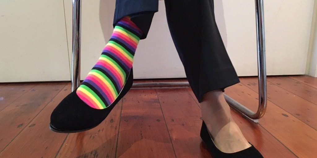 Woman's legs, sitting cross-legged on a chair, wearing black corporate style trousers, black court shoes and two different socks. You can see one foot has a rainbow coloured sock and the other a clear stocking sock. Does she need help with a decision of which pair to wear to work? What kind of decision-maker might she be?