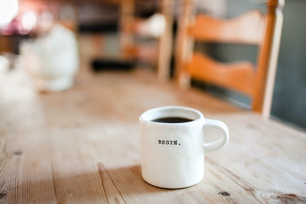 A white ceramic cup full of black coffee sits on a distressed timber table in the kitchen. It has the word 'Begin' in type-face capitals. The cup is clear in focus and the background is blurred.