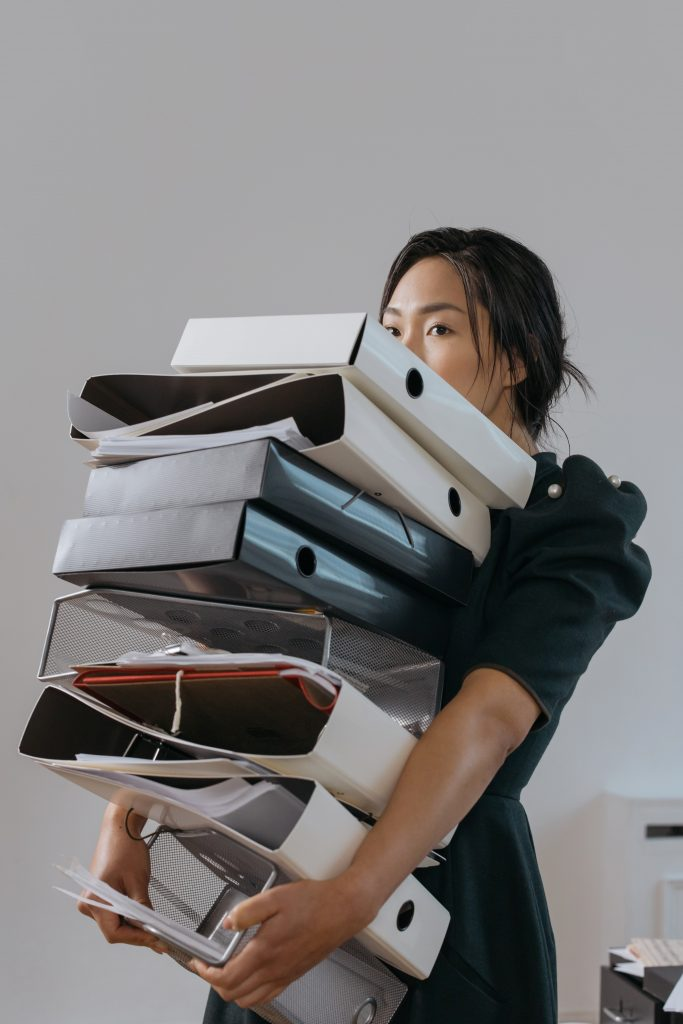 The image of a young woman with her arms full of a stack of folders represents a perfectionist type, typical of Imposter Syndrome. She may be someone who over-works to compensate for a lack of belief in her ability.