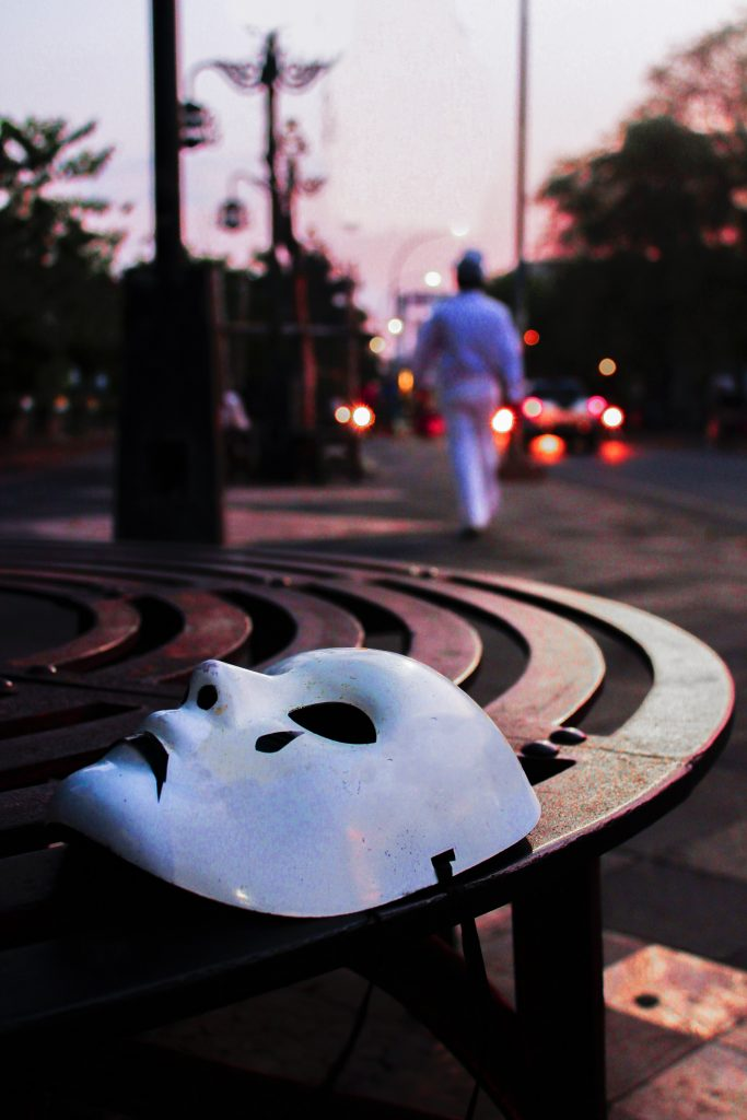 A white drama mask is discarded on a table in the park by a man who walks away as he heads towards the bright lights of the city. The drama mask represents Imposter Syndrome, which he needs to leave behind in order to enjoy his life, represented by the bright lights of city life.