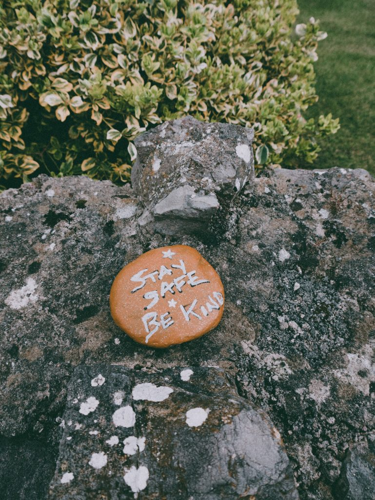 """The image is a caramel-coloured stone sitting on a grey craggy rock next to a green shrub on the edge of a garden with a mowed lawn. There is a message to passers-by inscribed on the stone: """"Stay safe, be kind"""". The image represents simple ways you can be kind and compassionate towards others, and remind yourself to do the same for you. Being kind and compassionate one of the suggested tips to cope mentally with COVID lockdown."""
