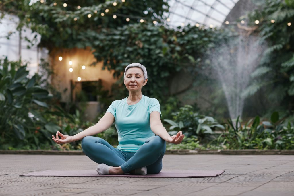 The image is a woman in her 60s, sitting cross-legged in Lotus position on a yoga mat in a lush green courtyard. She appears calm, peaceful and contemplative. Her eyes are closed and her arms outstretched with palms up, hands resting on her on her knees, with thumb and forefingers touching. Behind her, water sprays into the air and onto the garden. The courtyard is enclosed under a dome-style high roof with opaque glass, and opaque windows at the sides of the courtyard. The image represents the importance of practising gratitude, one of the suggested tips to cope mentally with COVID lockdown.