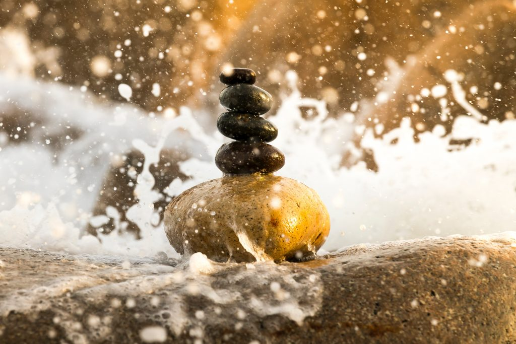 The image is a stack of four brown stones sitting on a medium sized yellow rock, which sits on a large boulder being battered by waves from the ocean. The froth of the surf surrounds the stones.